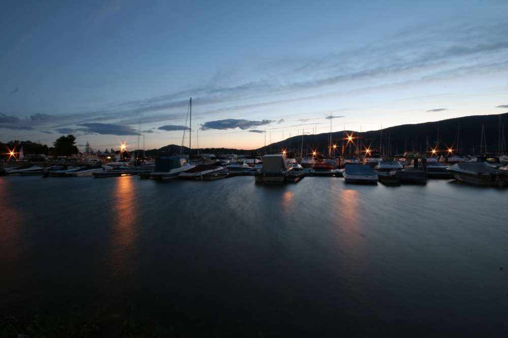 Boat silhouettes and marina lights on lake at sunset near vacation rental property in Kelowna Canada
