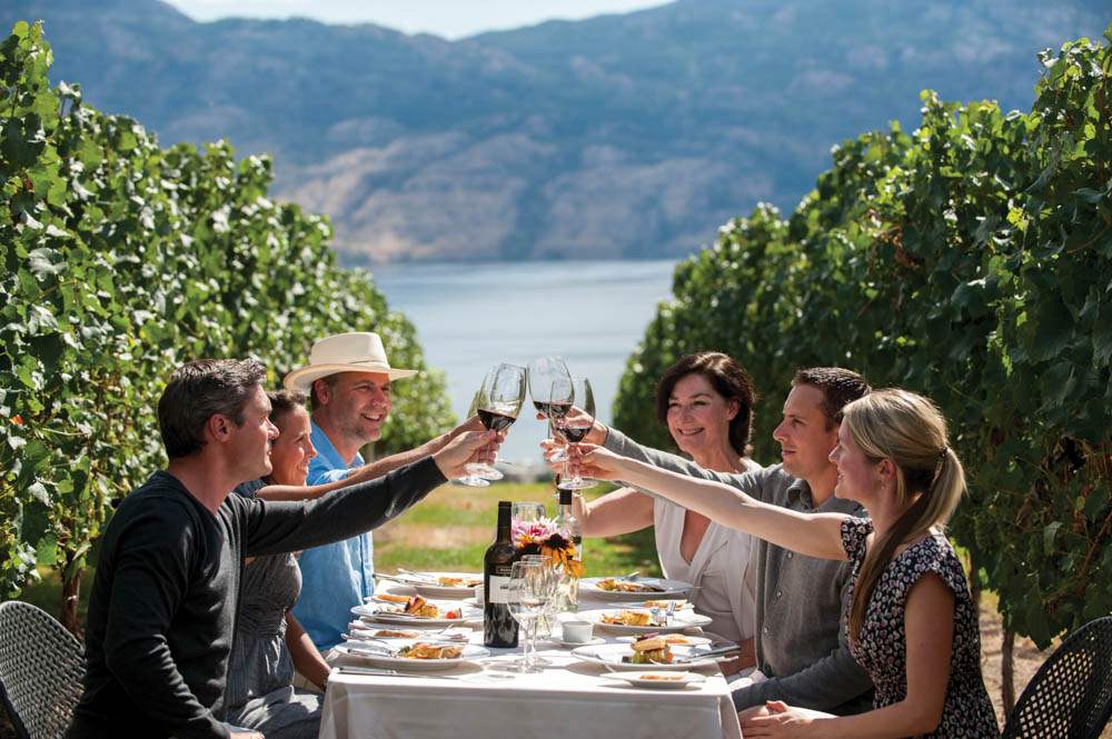 Group of friends toasting wine glasses while sitting at a table set for summer brunch in a vineyard near vacation rental in Kelowna Canada